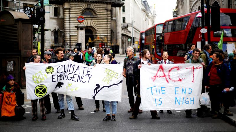 Extinction Rebellion climate change protesters held up banners as they briefly blocked the road near the Bank of England, in the City of London recently. Extinction Rebellion created blockades at various locations in the British capital for 10 days. (Photo: AP)