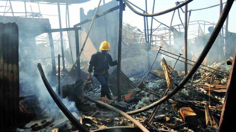 A fireman inspects the remains of a site at Prem Nagar, Dharavi where 100-odd shanties were destroyed in a devastating fire due to a short circuit. (Photo: Debasish Dey)