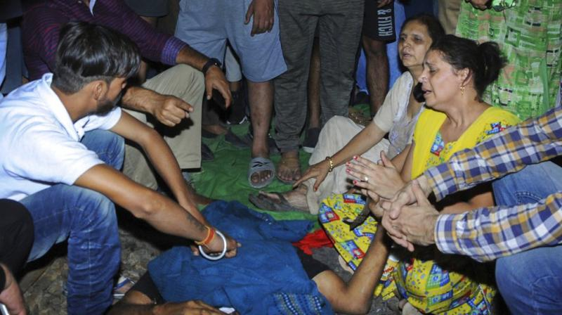 Relatives mourn near a victim at the site of a train accident at Joda Phatak in Amritsar. (Photo: PTI)