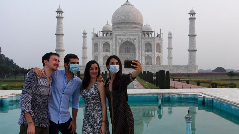 Tourists take pictures at the Taj Mahal which reopened on September 21, 2020. A study has found that much of the spread of Covid-19 was traceable to travel from Dubai and UK. (Representational image: (AFP)