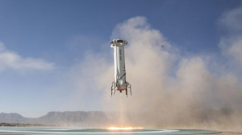 In this file photo provided by Blue Origin, the New Shepard booster lands in west Texas during a test. (Blue Origin via AP)