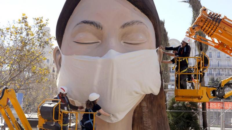 Workers place a mask on the figure of the Fallas festival in Valencia. AP photo