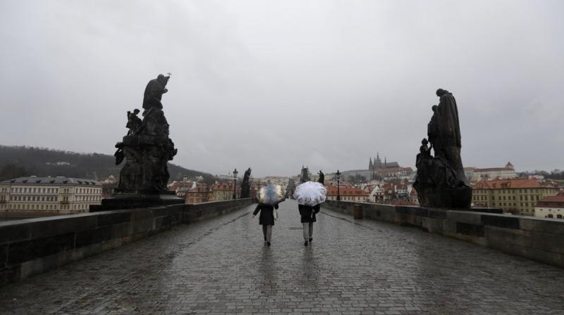 People walk across an unusually empty medieval Charles Bridge in Prague, Czech Republic. AP photo