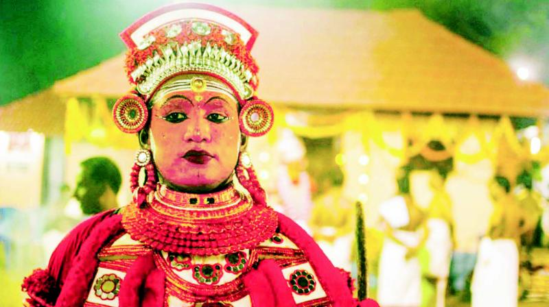 A Theyyakaran gets ready to perform during Theyyam