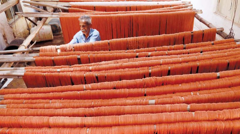 A weaver drying the washed yarns that were drenched in floods.(Photo: Arun Chandrabose)