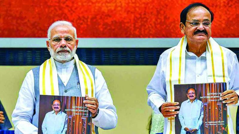 PM Narendra Modi and M. Venkaiah Naidu release a book during his first year as VP of India and Chairman of Rajya Sabha in New Delhi. (Photo: PTI)