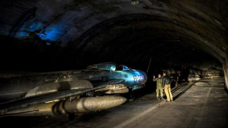 Albanian military personnel walk next to MIG-19 jet fighters inside the main tunnel of the Gjader Air Base built near the city of Lezhe. (Photo: AFP)