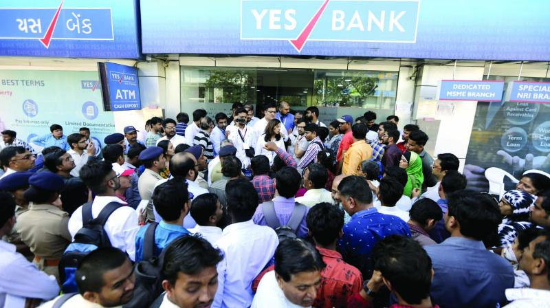 People wait for cash withdrawals outside a Yes Bank branch in Ahmedabad on Friday. (Photo: AP)