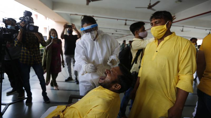A health worker takes swab sample of a devotee who will be participatinng in an annual Rath Yatra or chariot procession of Lord Jagannath at Jagannath temple in Ahmedabad. (Photo: PTI)