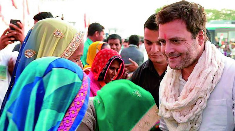 Congress President Rahul Gandhi being greeted by village women during an election campaign in Dahod, Gujarat. (Photo: PTI)