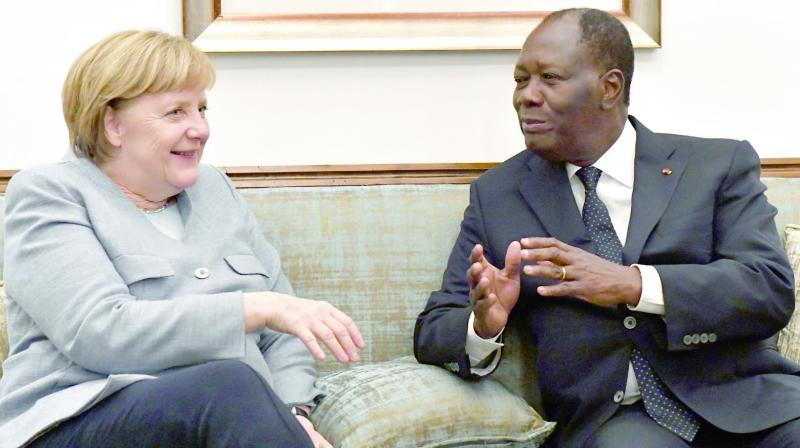 Ivorian President Alassane Ouattara, speaks with German chancellor Angela Merkel upon her arrival at the Felix Houphouet-Boigny airport in Abidjan on Wednesday, ahead of the Afican Union-European Union summit. (Photo: AFP)