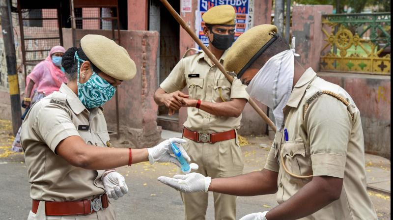 Indian cops using hand sanitizer to prevent the spread of coronavirus. (PTI)