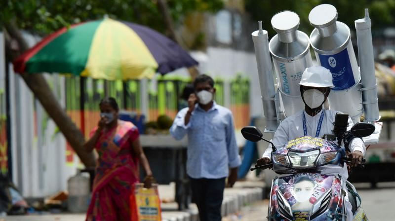A volunteer rides along a road with a mock Covishield and Covaxin vaccine vials on the back of his scooter during a Covid-19 coronavirus vaccination awareness campaign, in Chennai. (Photo: AFP)