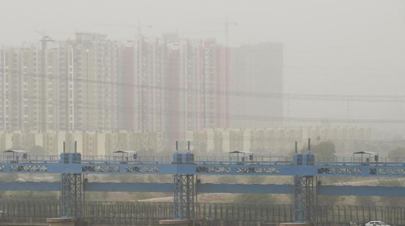 Vehicles cross a barrage on Hindon river as dust covers the skyline in Ghaziabad.  (Photo: AFP)