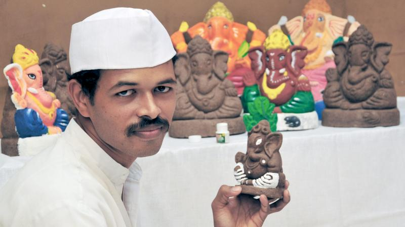 Nilesh Tupe gives the  finishing touches to cow dung idols in his studio at Nerul, Navi Mumbai. (Photo: Debasish Dey)