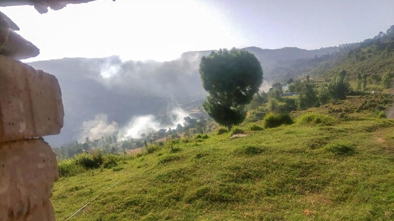 Smoke rises after a mortar shell was fired by Pakistani Army near the Line of Control (LoC), in Balakot sector of Poonch district. — PTI photo