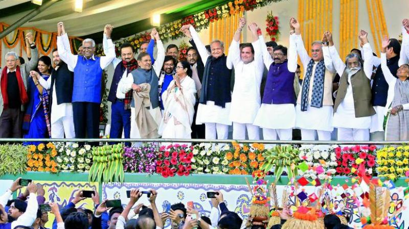 Newly sworn-in Jharkhand Chief Minister Hemant Soren with his father Shibu Soren, mother Rupi Soren, Congress leader Rahul Gandhi, West Bengal Chief Minister Mamata Banerjee, Rajasthan CM Ashok Gehlot, DMK leader M.K. Stalin, Left party leaders Sitaram Yechury and D. Raja, JDU's Sharad Yadav and other leaders join hands during the oath-taking ceremony at Morahabadi ground in Ranchi on Sunday.  (PTI)