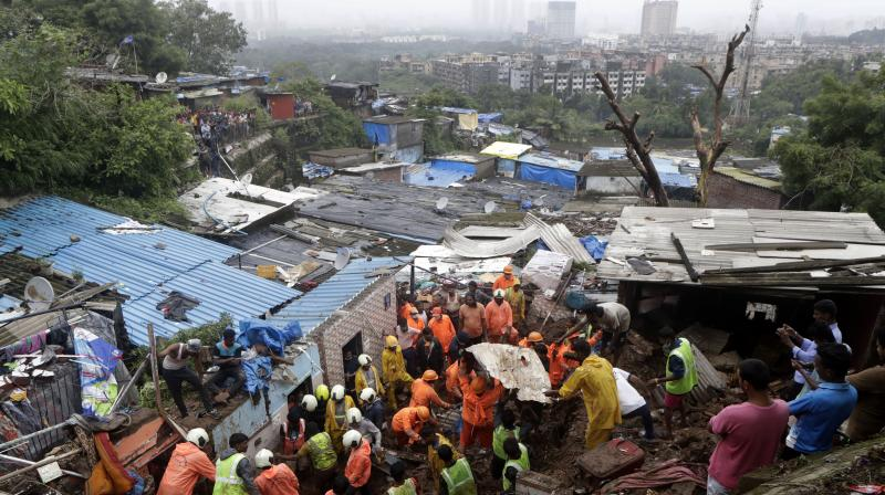 Rescuers look for survivors after a wall collapsed on several slum houses heavy monsoon rains in the Mahul area of Mumbai, India, Sunday, July 18, 2021. (Photo:AP)