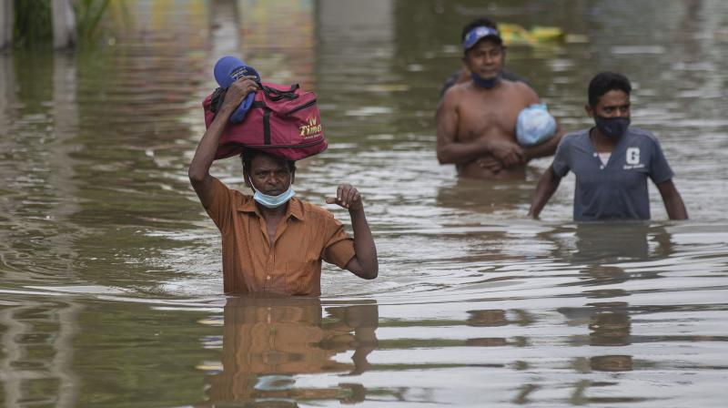 Sri Lankans wade through an inundated street following heavy rainfall at Malwana, on the outskirts of Colombo. (Photo: AP/PTI)