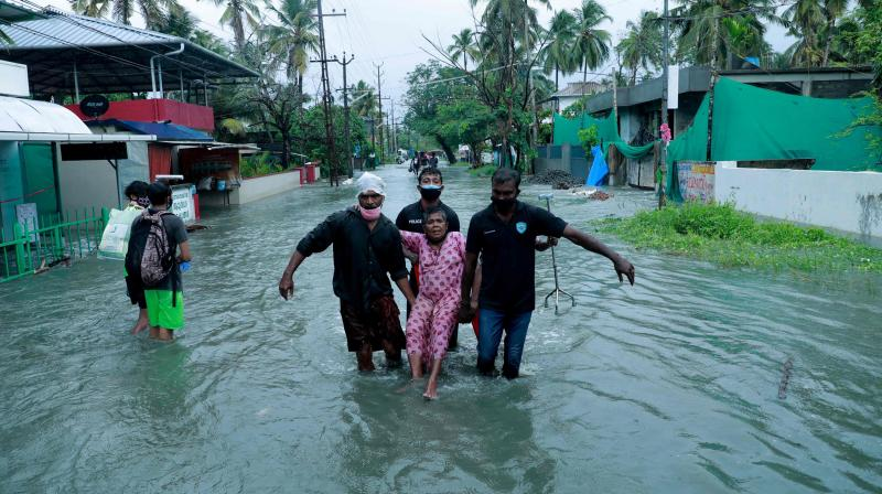 Police and rescue personnel evacuate a local resident through a flooded street in a coastal area after heavy rains under the influence of cyclone 'Tauktae' in Kochi on May 14, 2021. (Arunchandra BOSE / AFP)