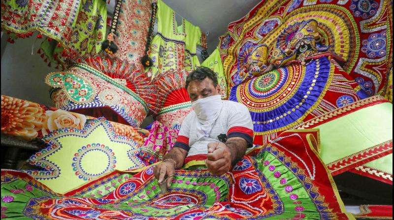 A tailor gives finishing touch to Lord Jagannath clothes ahead of Rath Yatra in Ahmedabad. PTI photo