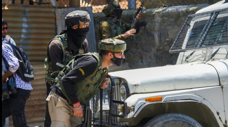 Security personnel take position behind a vehicle during an encounter with militants at Zoonimar area of Srinagar. PTI photo