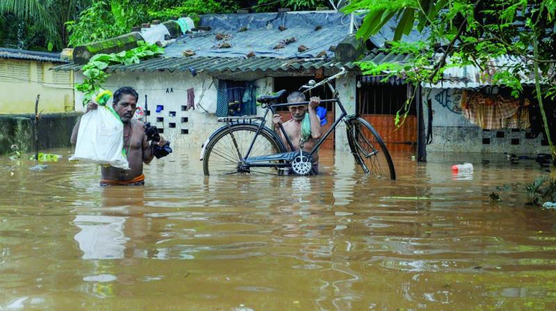 Villagers wade through flood waters at Bhoisahi in Bhubaneswar. (Photo: PTI)