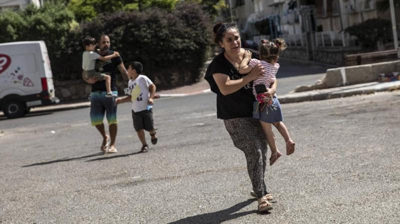 Lia Tal, 40, rushes with her children and partner to take shelter as a siren sounds a warning of incoming rockets fired from the Gaza Strip, In Ashdod, Israel, Thursday, May 20, 2021. (AP/Heidi Levine)
