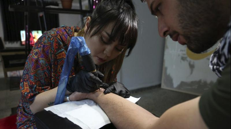 She's received death threats for taking on the taboo of the ink-on-skin drawings she does — as well as being a single woman willing to work with men. (Photo: AP)