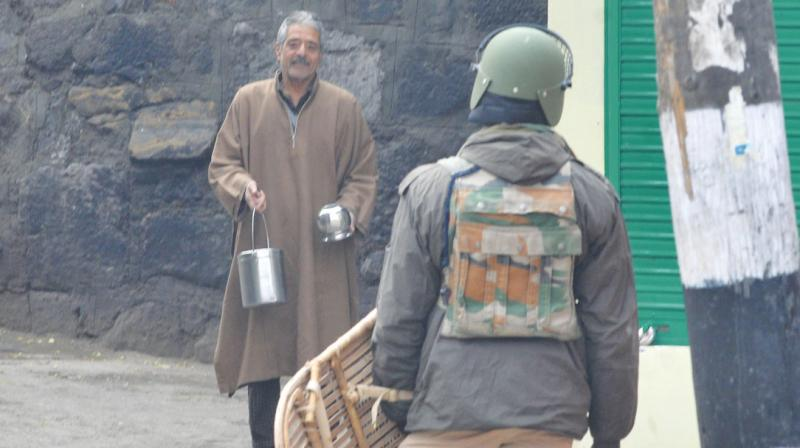 A resident pleads before a security force personnel to allow him to cross the road to fetch milk from the neighbourhood during curfew in central Srinagar. (Photo: H.U.Naqash)