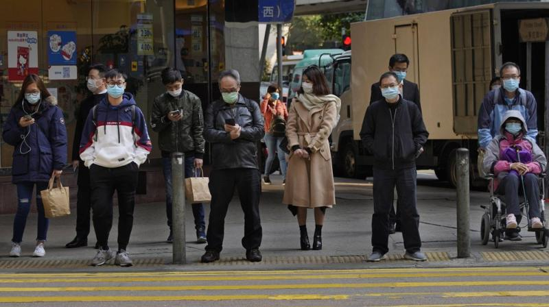 People wearing face mask stand at a downtown street in Hong Kong Monday, Feb. 17, 2020. COVID-19 viral illness has sickened tens of thousands of people in China since December. AP photo