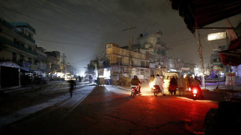People are silhouetted on vehicles headlights on a dark street during widespread power outages in Rawalpindi, Pakistan, Sunday, Jan. 10, 2021. Pakistan's national power grid experienced a major breakdown late night on Saturday, leaving millions of people in darkness, local media reported. (AP)