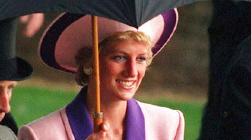 In this Wednesday, June 20, 1990 file photo, Britain's Princess Diana takes shelter under an umbrella while attending the second day of the Royal Ascot horse race meet near London. (Photo: AP)