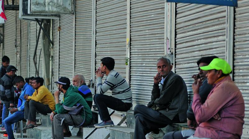 Traders sit outside locked shops during a protest against sealing in New Delhi on Saturday. — Biplab Banerjee