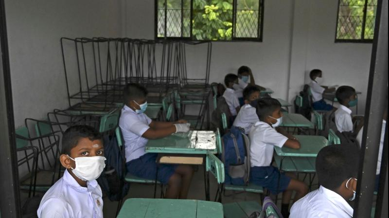 Students wearing facemasks sit in a classroom after their school was reopened in Colombo, Sri Lanka. AFP Photo
