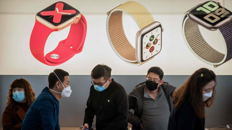In this picture taken on March 11, 2020 an Apple staff (C) and customers wearing face masks as a preventive measure against the COVID-19 coronavirus are seen inside of an Apple shop in Beijing. (Photo | AFP)