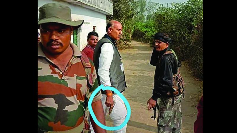 Congress candidate from Daltonganj K.N. Tripathi brandishes a revolver in Palamu district on Saturday during the first phase of Jharkhand Assembly elections. (Photo: PTI)