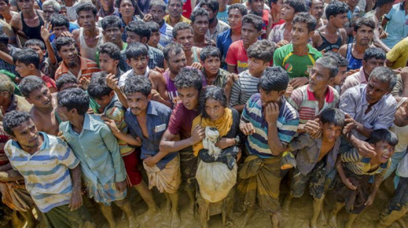 Rohingya Muslims, who crossed over from Myanmar into Bangladesh, wait to receive handouts near Balukhali refugee camp, Bangladesh. (Photo: AP)