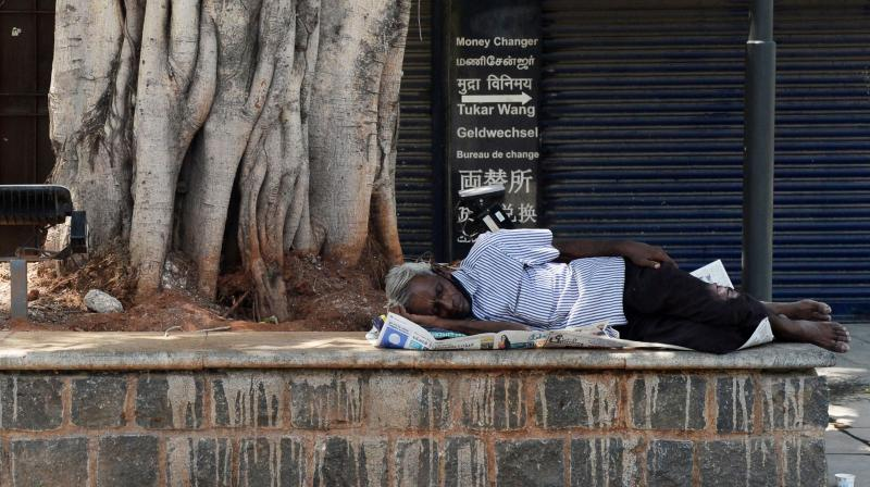 A man takes a nap under a tree in a closed commercial street after a lockdown was reimposed as a preventive measure against the spread of the COVID-19 coronavirus, in Chennai. AFP Photo