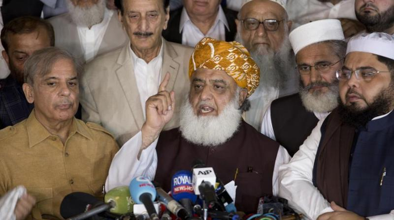 Maulana Fazlur Rehman, center, head of Pakistani religious parties alliance surrounds by Pakistani politicians addresses a news conference after the All Parties Conference (APC) in Islamabad, Pakistan, Friday, July 27, 2018. (Photo: AP)