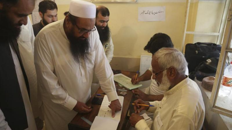 Hafiz Saeed, center, head of the Pakistani religious party Jamaat-ud-Dawa, affixes his thumb impression before casting a vote in Lahore, Pakistan, Wednesday, July 25, 2018. (Photo: AP)