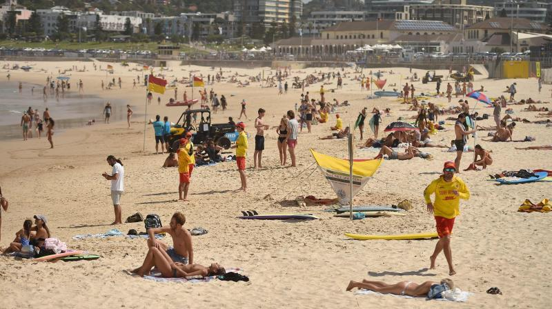 People sunbathe on Bondi Beach ahead of its closure in Sydney on Saturday. AFP Photo