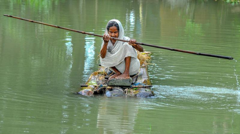 An elderly woman rows a makeshift raft to cross a flood-affected area of Mayong village in Morigaon district of Assam. PTI photo