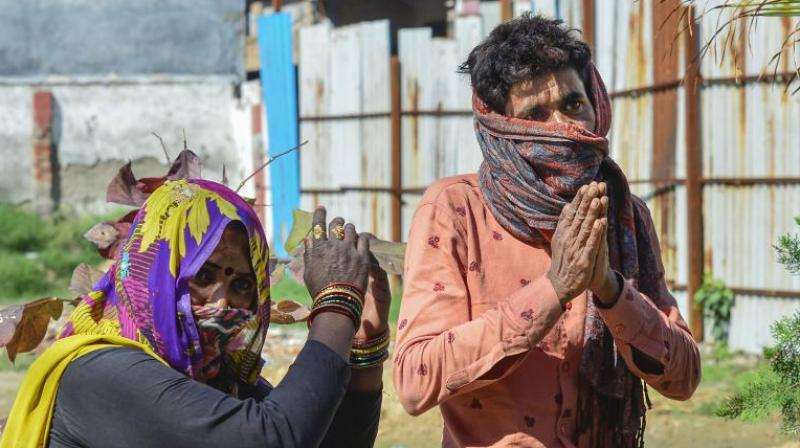 A migrant worker, suspected of coronavirus infection, and his wife beg a policeman to be allowed to go back to their native place, at a soup kitchen set up in New Delhi on March 27, 2020. (Photo- PTI)