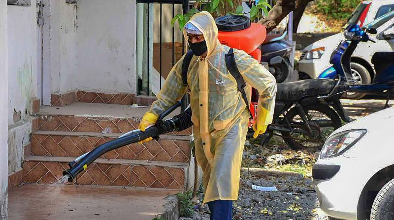 A BMC workers sprays disinfectant in the premises of a residential area to contain the spread of coronavirus during lockdown in Bhopal. PTI image