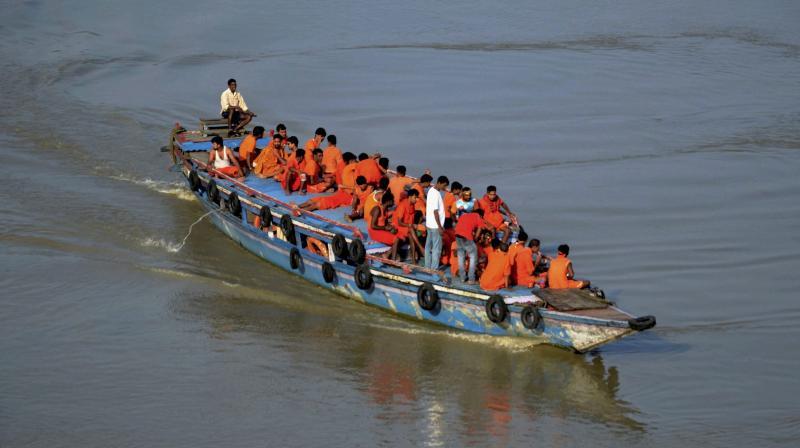 Kanwariyas travelling in a boat at river Brahmaputra in Guwahati. (Photo: PTI)