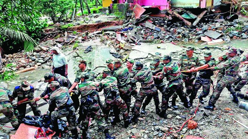 Soldiers clear the debris off a road in a flooded affected area at Wayanad.