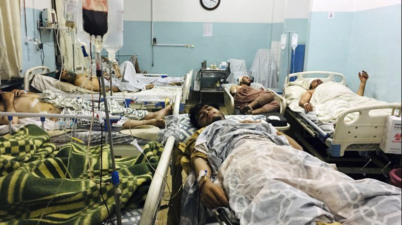 Wounded Afghans lie on a bed at a hospital after a deadly explosions outside the airport in Kabul, Afghanistan. (Photo: AP)