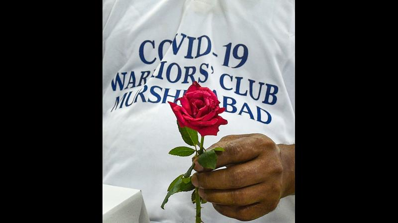 A COVID-19 recovered patient and part of Murshidabad COVID-19 warriors club holds a rose as he volunteers for coronavirus awareness campaign, in collaboration with the state government, at a hospital in Kolkata. (PTI)