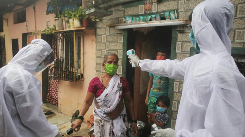 Health workers wearing personal protective equipment (PPE) conduct a door-to-door check-up of residents of Shivaji Nagar Slum for the detection of COVID-19 cases, at Malad in Mumbai. PTI photo